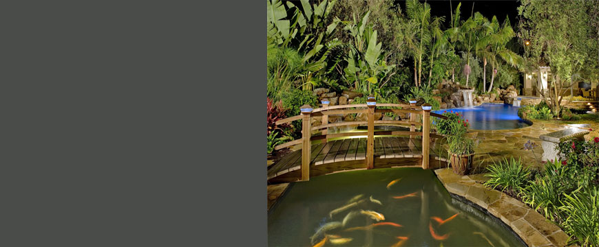 This elegant but natural back yard setting consists of beautiful natural stone decking combined with natural stone coping, stacked stone spa dam wall, natural bolder waterfall and pool bond beam, a large custom water fountain feature, large koi pond with a custom wood bridge and full size fireplace and hearth using stacked stone construction.