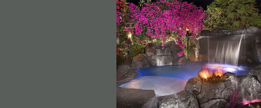 This exotic jungle lagoon spa is constructed entirely of man-made sculptured boulders, with man-made sculptured stone decking, including three fire elements, two main feature waterfalls with grotto seating, and a zero edge feature into a surrounding trough.