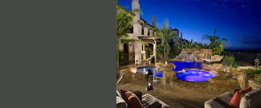 This rustic mountain retreat is constructed utilizing natural stone, artificial rock and random pavers to maintain the feel of a natural mountain setting. The pool is accented with a large rock waterfall, three unique fire features and an outdoor cooking/lounging area with a wooden open patio cover, barbecue, sink, lcemaker and refrigerator.