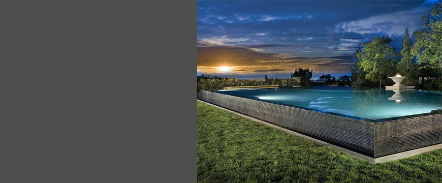 This unique project features a very large 1 250 sq. ft. raised four sided zero-edge pool and spa. It has specially selected glass tile surrounding the entire raised exterior of the pool enhancing the visual effects of the zero-edge design. There is a custom fire feature to simulate a floating caldron.