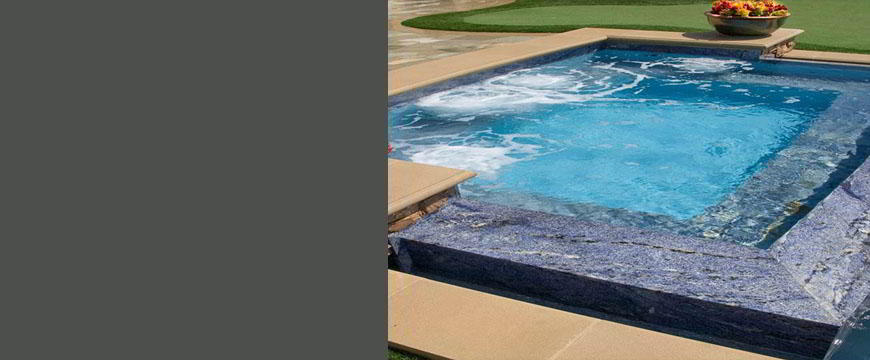 This elegant country club back yard is highlighted by this classic 8' raised zero-edge spa featuring custom colored poured-in-place concrete coping, unique one-of-a-kind blue granite surface hand cut and applied on the spa seat and the zero edge bond beam 30° sloped top and side walls with precision mitered corners.